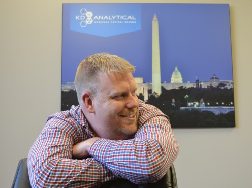 Director of Operations, Jon Terpening sits before a great photo of The Mall in Washington DC